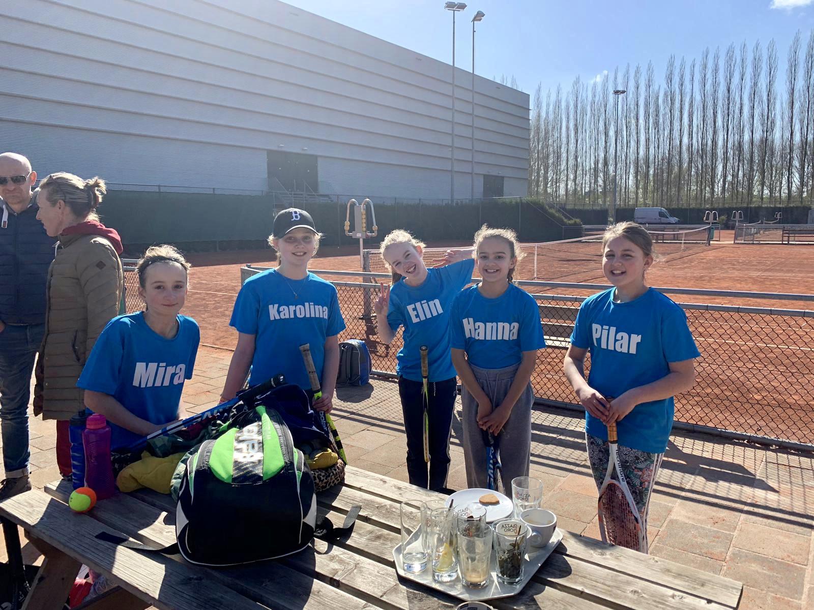 Een groep meisjes bij de tennisbaan